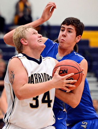 "Frederick's Ryan Miller (34) tries to shoot over Poudre's Sawyer Finley during the game at Frederick High School on Wednesday, Nov. 28, 2012.  Frederick beat Poudre 53-51.  For more photos visit  <a href=""http://www.BoCoPreps.com"">http://www.BoCoPreps.com</a>.<br /> (Greg Lindstrom/Times-Call)"