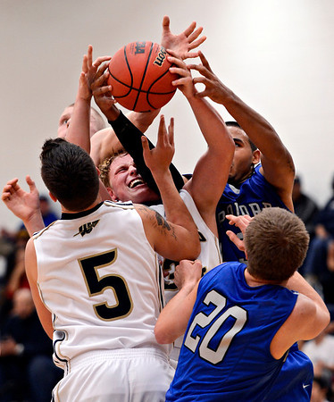 """Frederick's Ryan Miller, center, pulls down a rebound late in the fourth quarter during the game at Frederick High School on Wednesday, Nov. 28, 2012.  Frederick beat Poudre 53-51.  For more photos visit  <a href=""""http://www.BoCoPreps.com"""">http://www.BoCoPreps.com</a>.<br /> (Greg Lindstrom/Times-Call)"""
