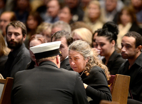 Retired Longmont firefighter Lynn Huff's wife Barbara Huff, right, is presented with the American flag during the funeral Friday morning Feb. 15, 2013 at LifeBridge Christian Church.<br /> (Lewis Geyer/Times-Call)