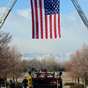 A giant American flag hangs between two ladder trucks for the funeral of retired Longmont firefighter Lynn Huff Friday morning Feb. 15, 2013 at LifeBridge Christian Church. (Lewis Geyer/Times-Call)