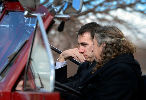 Retired Longmont firefighter Lynn Huff's son Christopher Huff, left, and wife Barbara Huff, right, sit in an antique fire truck at his funeral Friday morning Feb. 15, 2013 at LifeBridge Christian Church.<br /> (Lewis Geyer/Times-Call)