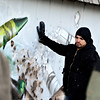 """Gamma Acosta holds a wall Monday, Dec. 24, 2012, containing his mural painted as a tribute to Sandy Hook. The wall is being cut out to preserve the artwork. For more photos and a video visit  <a href=""""http://www.TimesCall.com"""">http://www.TimesCall.com</a>.<br /> (Greg Lindstrom/Times-Call)"""