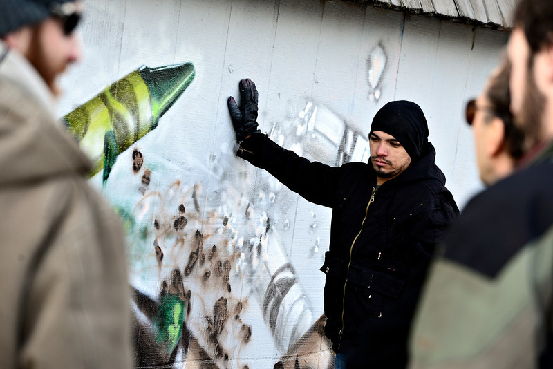 "Gamma Acosta holds a wall Monday, Dec. 24, 2012, containing his mural painted as a tribute to Sandy Hook. The wall is being cut out to preserve the artwork. For more photos and a video visit  <a href=""http://www.TimesCall.com"">http://www.TimesCall.com</a>.<br /> (Greg Lindstrom/Times-Call)"