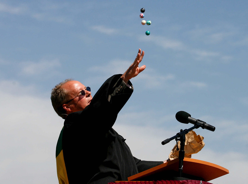 Retiring Silver Creek High School social studies teacher Kent Willmann tosses a handful of small rubber balls to the graduates at the close of his speech to the school's graduating class, May 29, 2010.