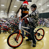 "Daniel Corneleo, 11, chooses a new bike with the assistance of volunteer Alexann Riddle during the annual Y-Pals Holiday Party and Longmont Bicycle Giveaway at the Ed & Ruth Lehman YMCA, 950 Lashley St., Saturday Dec. 15, 2012. Nearly 580 bikes were collected through the annual holiday bike program sponsored by Bicycle Longmont. TO VIEW A VIDEO AND SLIDESHOW VISIT  <a href=""http://WWW.TIMESCALL.COM"">http://WWW.TIMESCALL.COM</a> (Lewis Geyer/Times-Call)"