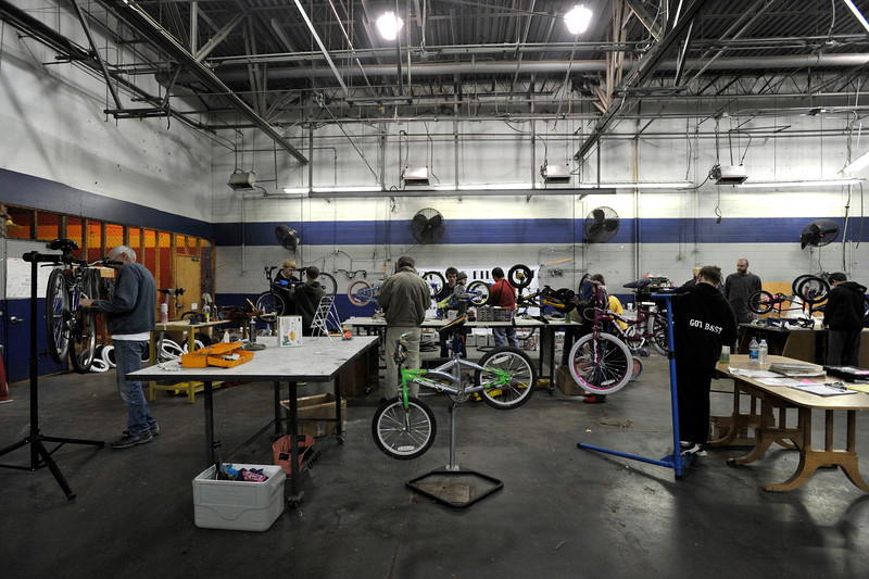 Volunteers and Boys Scouts from Troop No. 36 work to clean, fix and organize bikes, Wednesday, Nov. 28, 2012, at Bicycle Longmont's Bike Garage at Twin Peaks Mall.<br /> (Matthew Jonas/Times-Call)