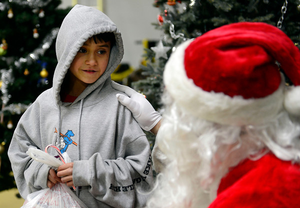"""Saul Corneleo, 9, visits with Santa Claus during the annual Y-Pals Holiday Party and Longmont Bicycle Giveaway at the Ed & Ruth Lehman YMCA, 950 Lashley St., Saturday Dec. 15, 2012. TO VIEW A VIDEO AND SLIDESHOW VISIT  <a href=""""http://WWW.TIMESCALL.COM"""">http://WWW.TIMESCALL.COM</a> (Lewis Geyer/Times-Call)"""