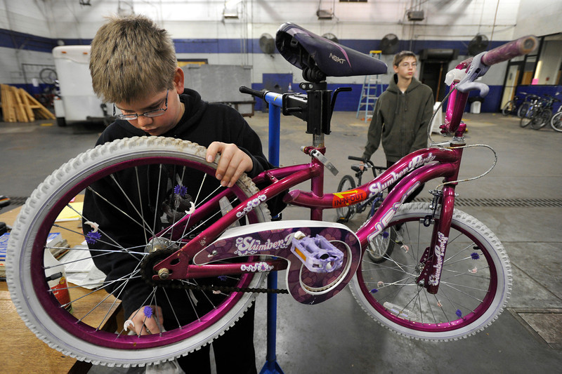 Mark Lovstedt, Boy Scout Troop No. 360, works to clean a bike, Wednesday, Nov. 28, 2012, at Bicycle Longmont's Bike Garage at Twin Peaks Mall.<br /> (Matthew Jonas/Times-Call)