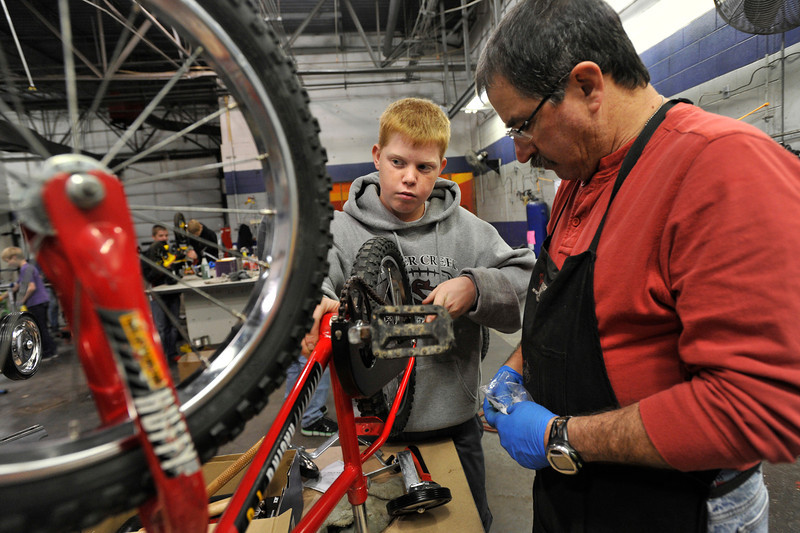 From left: Josh Brague, Boy Scout Troop No. 360, works with bike mechanic Buzz Feldman to install training wheels, Wednesday, Nov. 28, 2012, at Bicycle Longmont's Bike Garage at Twin Peaks Mall.<br /> (Matthew Jonas/Times-Call)