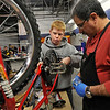 From left: Josh Brague, Boy Scout Troop No. 360, works with bike mechanic Buzz Feldman to install training wheels, Wednesday, Nov. 28, 2012, at Bicycle Longmont's Bike Garage at Twin Peaks Mall.<br /> (Matthew Jonas/Times-Call)