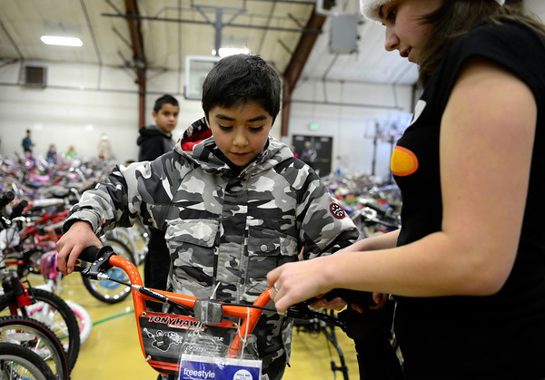 """Daniel Corneleo, 11, chooses a new bike with the assistance of volunteer Alexann Riddle during the annual Y-Pals Holiday Party and Longmont Bicycle Giveaway at the Ed & Ruth Lehman YMCA, 950 Lashley St., Saturday Dec. 15, 2012. Nearly 580 bikes were collected through the annual holiday bike program sponsored by Bicycle Longmont. TO VIEW A VIDEO AND SLIDESHOW VISIT  <a href=""""http://WWW.TIMESCALL.COM"""">http://WWW.TIMESCALL.COM</a> (Lewis Geyer/Times-Call)"""