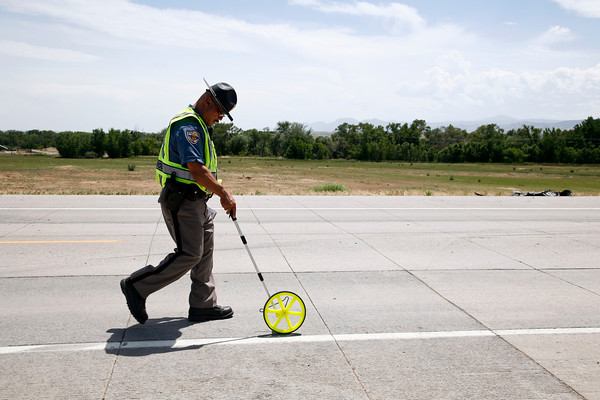 A Colorado State Patrol trooper investigates the scene after a two-car accident on State Highway 66 in front of the Greenwood Wildlife Rehabilitation Center in Longmont, Friday, June 28, 2013. (Kai Casey/Times-Call)