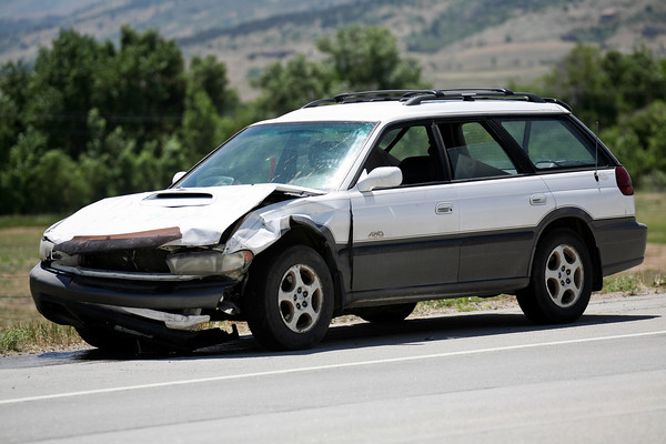 A wrecked car sits on the side of the road after a two-car accident on State Highway 66 in front of the Greenwood Wildlife Rehabilitation Center in Longmont, Friday, June 28, 2013. (Kai Casey/Times-Call)