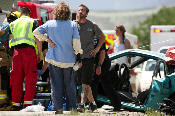 A man reacts to the accident as emergency personnel work to get a woman who was pinned in her car after a two-car accident on State Highway 66 in front of the Greenwood Wildlife Rehabilitation Center in Longmont, Friday, June 28, 2013. (Kai Casey/Times-Call)
