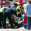 Emergency personnel work to get a woman who was pinned in her car after a two-car accident on State Highway 66 in front of the Greenwood Wildlife Rehabilitation Center in Longmont, Friday, June 28, 2013. (Kai Casey/Times-Call)