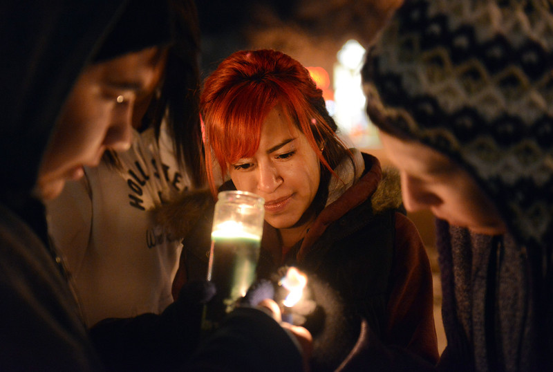 Ana Lopez, 17, helps light a candle during a vigil for 16 year old Jason Grimmer Tuesday night Jan. 01, 2013. Grimmer died after being struck by a hit-and-run vehicle on North Main Street. (Lewis Geyer/Times-Call)