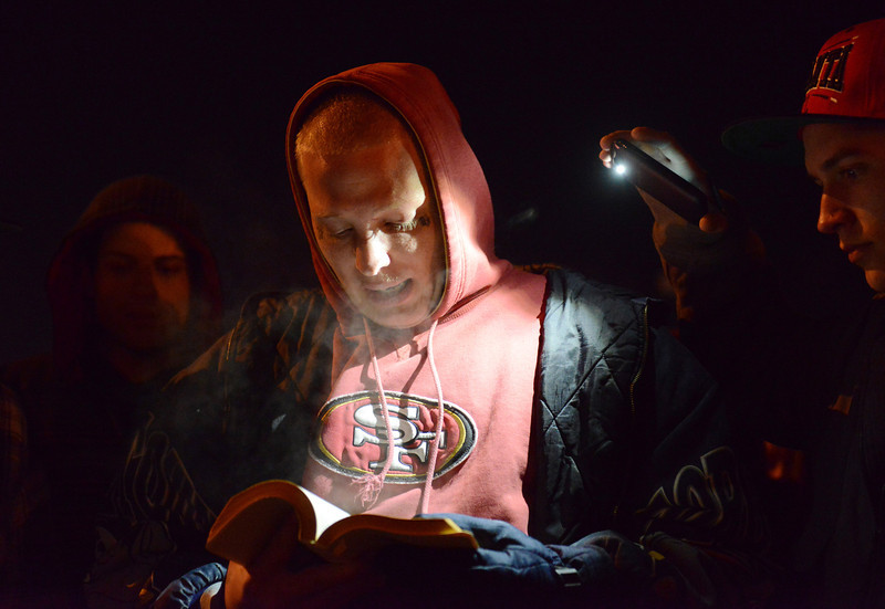 Derek Baringa, a friend of Jason Grimmer, reads from the Bible during a vigil Tuesday night, Jan. 1, 2013. Grimmer died after being struck by a hit-and-run vehicle on North Main Street. (Lewis Geyer/Times-Call)