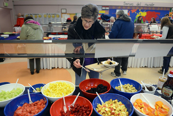 Cheryl Parrish, of Windsor, chooses from a variety of toppings for her bowl of oatmeal at the 17th annual Oatmeal Festival in Lafayette Saturday morning Jan. 12, 2013. (Lewis Geyer/Times-Call)