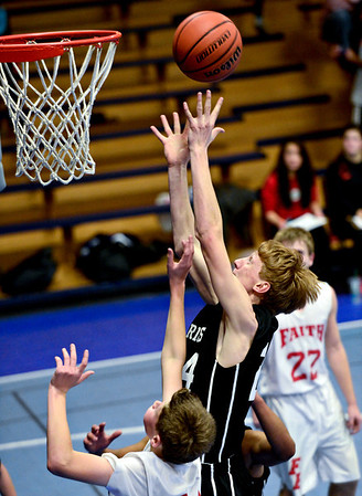 """Longmont Christian's Cole Moffitt reaches for a rebound over Faith Baptist's Caleb Pene during the game at the St. Vrain Memorial Building in Longmont on Friday, Nov. 30, 2012. Longmont Christian won 66-46. For more photos visit  <a href=""""http://www.BoCoPreps.com"""">http://www.BoCoPreps.com</a>.<br /> (Greg Lindstrom/Times-Call)"""