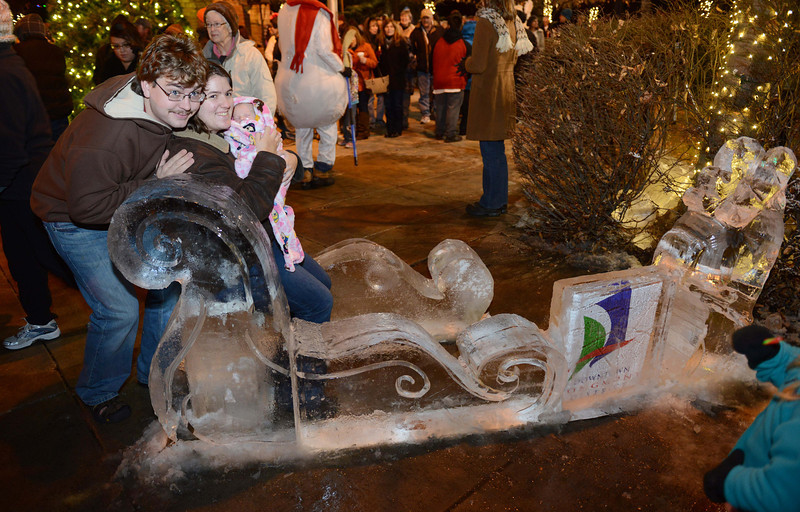 "Daniel Watson, Kimberl Parreira, and Liana Parreira, who was nine days old, have their photo taken in an ice-carved sleigh during the ""Hooray, Hooray for the Holidays"" downtown tree lighting ceremony Friday night Nov. 23, 2012 at Sixth Avenue and Main Street. Hundreds were entertained with caroling and a host of holiday characters as the 17-foot tree was lit.(Lewis Geyer/Times-Call)"