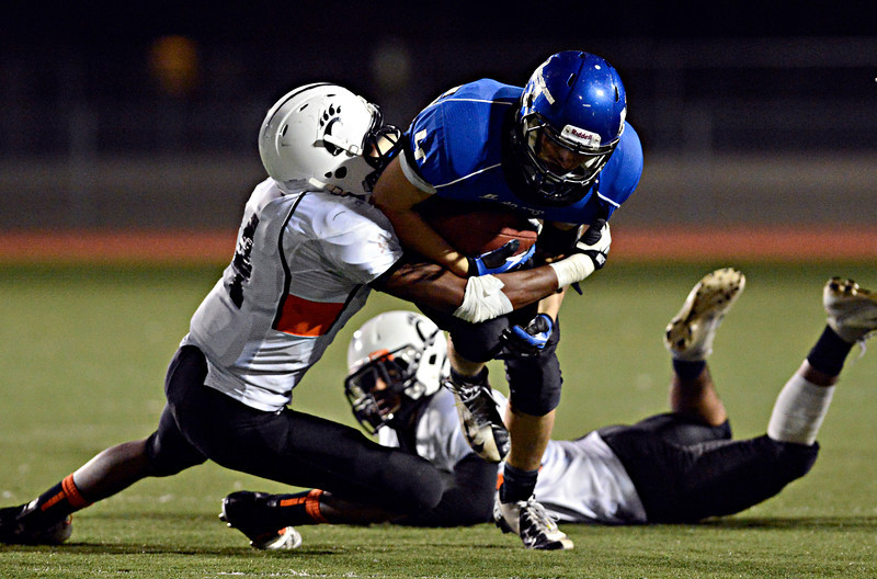 """Longmont's Drake Greeott tries to break through a tackle by Greeley Central's Devonte Davis during the game at Longmont High School on Friday, Nov. 2, 2012. Longmont beat Greeley Central 42-25. For more photos visit  <a href=""""http://www.BoCoPreps.com"""">http://www.BoCoPreps.com</a>.<br /> (Greg Lindstrom/Times-Call)"""