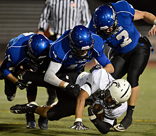 "Longmont defenders, left to right, Brody Rothe, Isaac Sprecher and Ryan Jacques bring down Greeley Central's Andres Ortega during the game at Longmont High School on Friday, Nov. 2, 2012. Longmont beat Greeley Central 42-25. For more photos visit  <a href=""http://www.BoCoPreps.com"">http://www.BoCoPreps.com</a>.<br /> (Greg Lindstrom/Times-Call)"