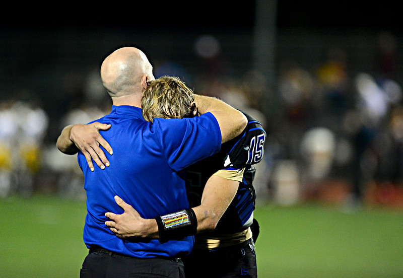 """Longmont's Forrest Wetterstrom (15) and head coach Doug Johnson embrace after the game.  Windsor beat Longmont 27-17 at Everly-Montgomery Field in Longmont on Friday, Sept. 28, 2012.  For more photos visit  <a href=""""http://www.BoCoPreps.com"""">http://www.BoCoPreps.com</a>.<br /> (Greg Lindstrom/Times-Call)"""
