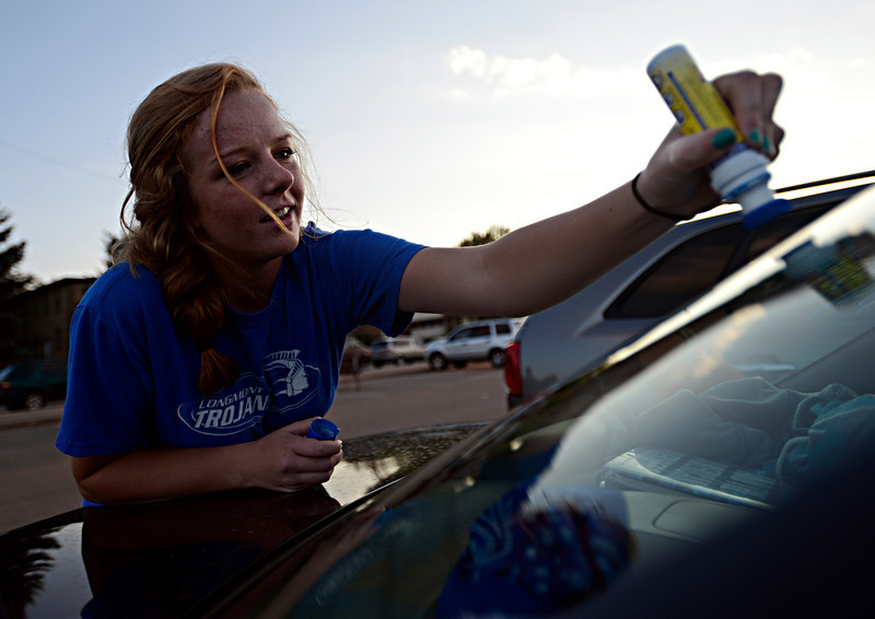 """Longmont junior Lauren Offutt paints her friend's car before the game at Longmont High School.  Windsor beat Longmont 27-17 at Everly-Montgomery Field in Longmont on Friday, Sept. 28, 2012.  For more photos visit  <a href=""""http://www.BoCoPreps.com"""">http://www.BoCoPreps.com</a>.<br /> (Greg Lindstrom/Times-Call)"""