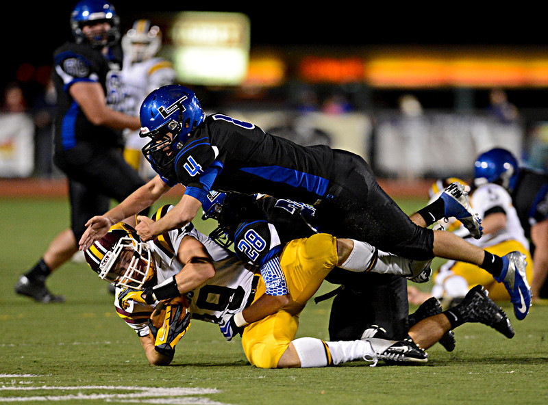 """Longmont's Brody Rothe (4) and Marcus Vasquez (28) bring down Windsor's Alex Baldwin (19) in the second half.  Windsor beat Longmont 27-17 at Everly-Montgomery Field in Longmont on Friday, Sept. 28, 2012.  For more photos visit  <a href=""""http://www.BoCoPreps.com"""">http://www.BoCoPreps.com</a>.<br /> (Greg Lindstrom/Times-Call)"""
