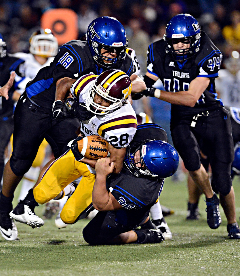 """Windsor's Jordan Porterfield (28) is brought down by Longmont's Joe Lopez (26) and Marcus Johnson (18) in the first half.  Longmont hosts Windsor during homecoming at Everly-Montgomery Field in Longmont on Friday, Sept. 28, 2012.  For more photos visit  <a href=""""http://www.BoCoPreps.com"""">http://www.BoCoPreps.com</a>.<br /> (Greg Lindstrom/Times-Call)"""