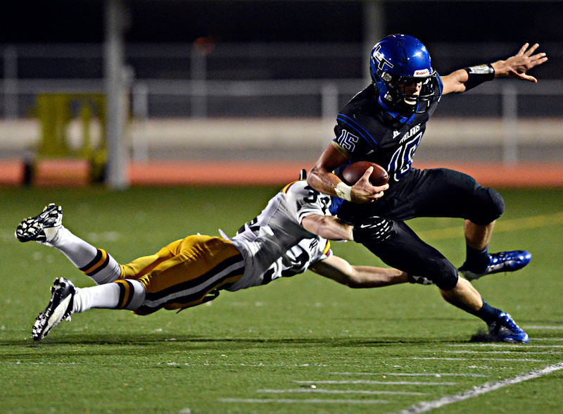 """Longmont quarterback Forrest Wetterstrom (15) is pushed out of bounds by Windsor's Duncan Goodrich in the first half.  Longmont hosts Windsor during homecoming at Everly-Montgomery Field in Longmont on Friday, Sept. 28, 2012.  For more photos visit  <a href=""""http://www.BoCoPreps.com"""">http://www.BoCoPreps.com</a>.<br /> (Greg Lindstrom/Times-Call)"""