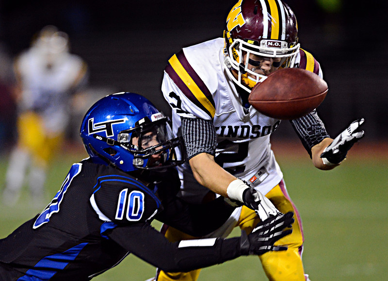 """Longmont's Spencer Zuege (10) competes for a ball with Windsor's Lance Cox (2) during a Longmont fourth-down near the end of the fourth quarter.  Windsor beat Longmont 27-17 at Everly-Montgomery Field in Longmont on Friday, Sept. 28, 2012.  For more photos visit  <a href=""""http://www.BoCoPreps.com"""">http://www.BoCoPreps.com</a>.<br /> (Greg Lindstrom/Times-Call)"""