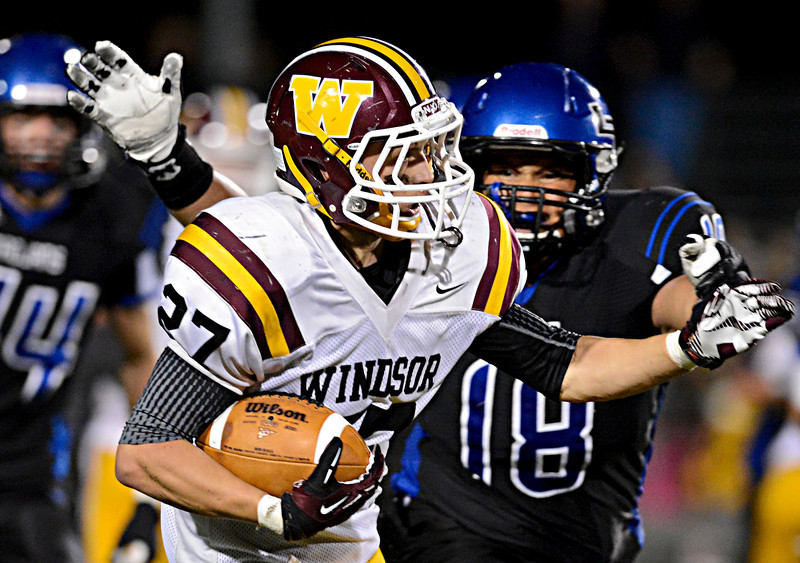 """Longmont's Marcus Johnson (18) tries to bring down Windsor's Brandon King (27) in the second half.  Windsor beat Longmont 27-17 at Everly-Montgomery Field in Longmont on Friday, Sept. 28, 2012.  For more photos visit  <a href=""""http://www.BoCoPreps.com"""">http://www.BoCoPreps.com</a>.<br /> (Greg Lindstrom/Times-Call)"""