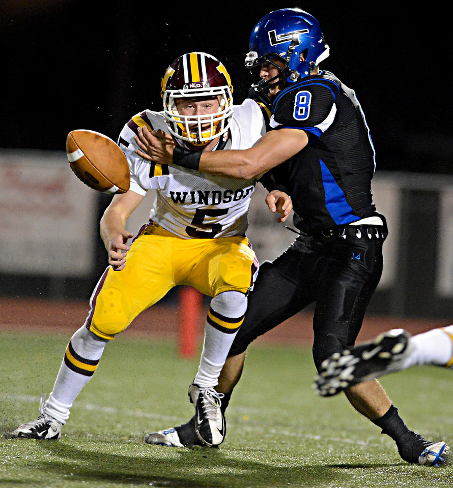 """Longmont's Drew Magee (8) forces a fumble by Windsor's Joseph Sanger (5) in the second half.  Windsor beat Longmont 27-17 at Everly-Montgomery Field in Longmont on Friday, Sept. 28, 2012.  For more photos visit  <a href=""""http://www.BoCoPreps.com"""">http://www.BoCoPreps.com</a>.<br /> (Greg Lindstrom/Times-Call)"""