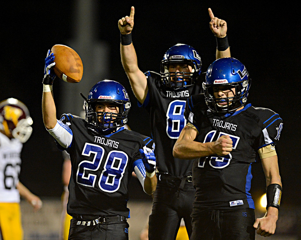 """Longmont's Marcus Vasquez (28), Drew Magee (8) and Forrest Wetterstrom (15) celebrate after a Windsor fumble in the second half.  The fumble was forced by Magee and recovered by Vasquez.  Windsor beat Longmont 27-17 at Everly-Montgomery Field in Longmont on Friday, Sept. 28, 2012.  For more photos visit  <a href=""""http://www.BoCoPreps.com"""">http://www.BoCoPreps.com</a>.<br /> (Greg Lindstrom/Times-Call)"""