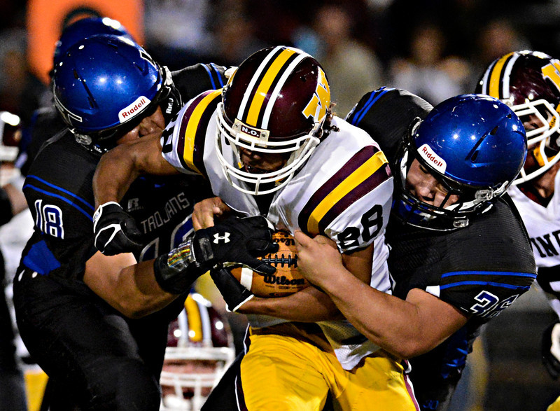 "Windsor's Jordan Porterfield (28) is brought down by Longmont's Joe Lopez (26) and Marcus Johnson (18) in the first half.    Windsor beat Longmont 27-17 at Everly-Montgomery Field in Longmont on Friday, Sept. 28, 2012.  For more photos visit  <a href=""http://www.BoCoPreps.com"">http://www.BoCoPreps.com</a>.<br /> (Greg Lindstrom/Times-Call)"