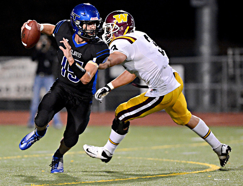 """Longmont quarterback Forrest Wetterstrom (15) evades a tackle by Windsor's Sean Glenn (3) in the first half.  Longmont hosts Windsor during homecoming at Everly-Montgomery Field in Longmont on Friday, Sept. 28, 2012.  For more photos visit  <a href=""""http://www.BoCoPreps.com"""">http://www.BoCoPreps.com</a>.<br /> (Greg Lindstrom/Times-Call)"""