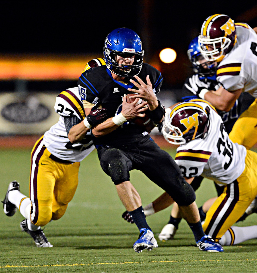 """Longmont quarterback Forrest Wetterstrom (15) tries to hold onto the ball as he is tackled by Windsor's Brandon King, left, in the first half.  Longmont hosts Windsor during homecoming at Everly-Montgomery Field in Longmont on Friday, Sept. 28, 2012.  For more photos visit  <a href=""""http://www.BoCoPreps.com"""">http://www.BoCoPreps.com</a>.<br /> (Greg Lindstrom/Times-Call)"""