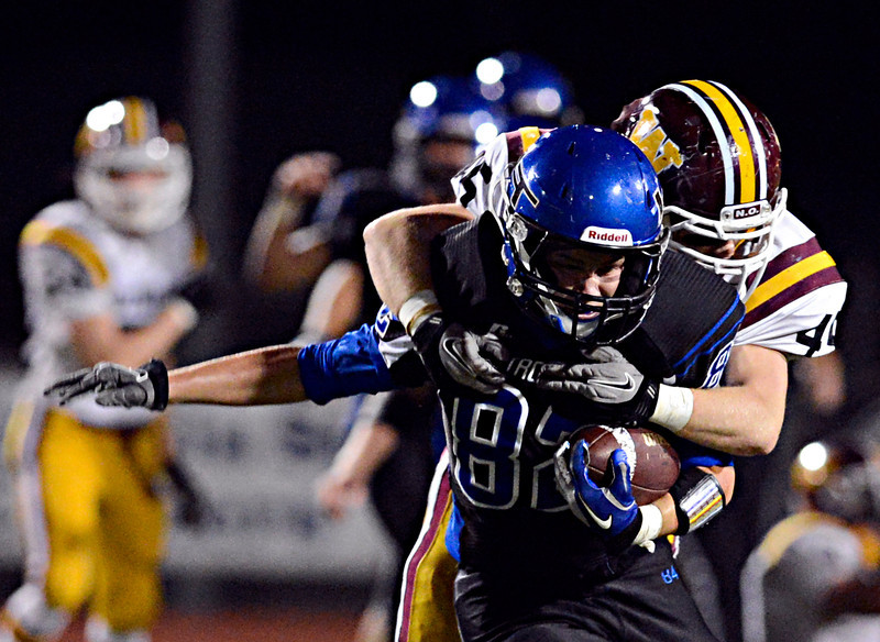 """Longmont's Duncan McCabe (82) is tackled by Windsor's Sean McAvoy in the first half.  Longmont hosts Windsor during homecoming at Everly-Montgomery Field in Longmont on Friday, Sept. 28, 2012.  For more photos visit  <a href=""""http://www.BoCoPreps.com"""">http://www.BoCoPreps.com</a>.<br /> (Greg Lindstrom/Times-Call)"""