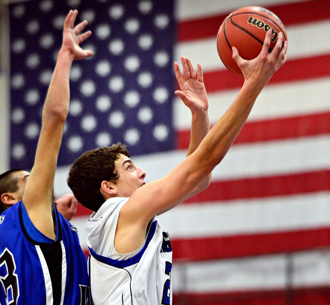"""Longmont's Austin Kemp goes up for a shot over Fort Lupton's Jalen Vasquez during the game at Longmont High School on Tuesday, Dec. 4, 2012. Longmont beat Fort Lupton 47-34. For more photos visit  <a href=""""http://www.BoCoPreps.com"""">http://www.BoCoPreps.com</a>.<br /> (Greg Lindstrom/Times-Call)"""