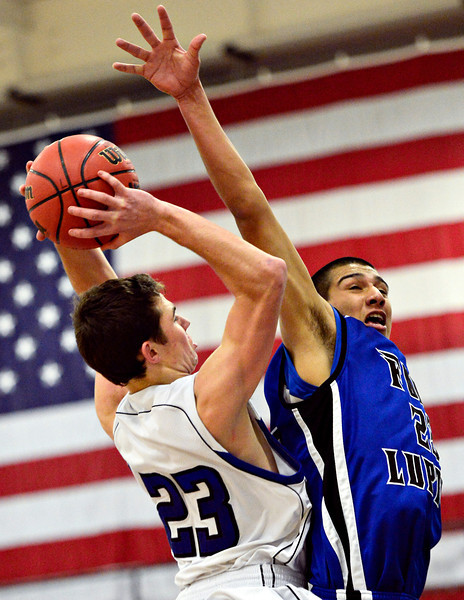 """Longmont's Eli Sullivan, left, goes up for a shot against Fort Lupton's Jalen Vasquez during the game at Longmont High School on Tuesday, Dec. 4, 2012. Longmont beat Fort Lupton 47-34. For more photos visit  <a href=""""http://www.BoCoPreps.com"""">http://www.BoCoPreps.com</a>.<br /> (Greg Lindstrom/Times-Call)"""