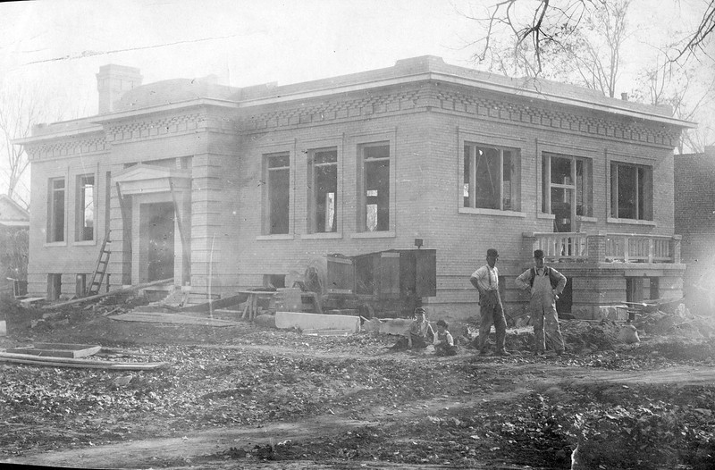 An earlier stage of construction. One of the men in the bowler style<br /> hats may be Frank Wiggins, but isn't specifically identified.<br /> (Courtesy Longmont Museum)
