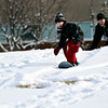 Evan Lennert, 7, eyes a jump while riding down the hill at Skyline High School while his dad, Chris, watches in Longmont on Tuesday, Dec. 25, 2012. <br /> (Greg Lindstrom/Times-Call)