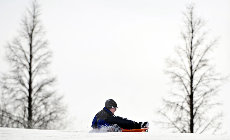 Noah Lennert, 10, enjoys a ride down the hill at Skyline High School in Longmont on Tuesday, Dec. 25, 2012. <br /> (Greg Lindstrom/Times-Call)