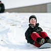 Evan Lennert, 7, enjoys a ride down the hill at Skyline High School while his dad, Chris, watches in Longmont on Tuesday, Dec. 25, 2012. <br /> (Greg Lindstrom/Times-Call)