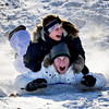 Sisters Jessica Calzolari, top, 17, and Emily, 15, react after nearly hitting a snowboarder while sledding at Sunset Middle School in Longmont on Tuesday, Dec. 25, 2012. <br /> (Greg Lindstrom/Times-Call)