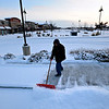 Jeremy Diaz, with Made in the Shade Landscaping, clears snow from a sidewalk in the Harvest Junction complex in Longmont on Tuesday, Dec. 25, 2012. <br /> (Greg Lindstrom/Times-Call)