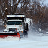 A snow plow works to clear Longs Peak Avenue in Longmont on Tuesday, Dec. 25, 2012. <br /> (Greg Lindstrom/Times-Call)