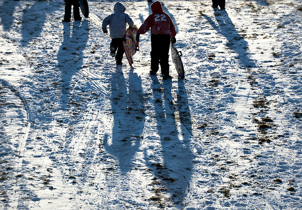 Sledders run up the hill at Sunset Middle School in Longmont on Tuesday, Dec. 25, 2012. <br /> (Greg Lindstrom/Times-Call)