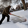 Brandon Noe clears snow from a sidewalk in Longmont on Tuesday, Dec. 25, 2012. <br /> (Greg Lindstrom/Times-Call)